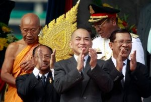 Cambodia's King Norodom Sihamoni, center, claps altogether with Prime Minister Hun Sen, right, and Heng Samrin, second left, National Assembly President, during the Independence Day celebration at the Independence Monument in Phnom Penh, Cambodia, Tuesday, Nov. 9, 2010. King Sihamoni is jointed by thousand of civil servants and students to mark the country's 57th Independence Day from France, Nov. 9, 1953. (AP Photo/Heng Sinith)